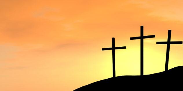 Das Bild zeigt drei Kreuze auf einem Berg,© iStockPhoto / KimsCreativeHub