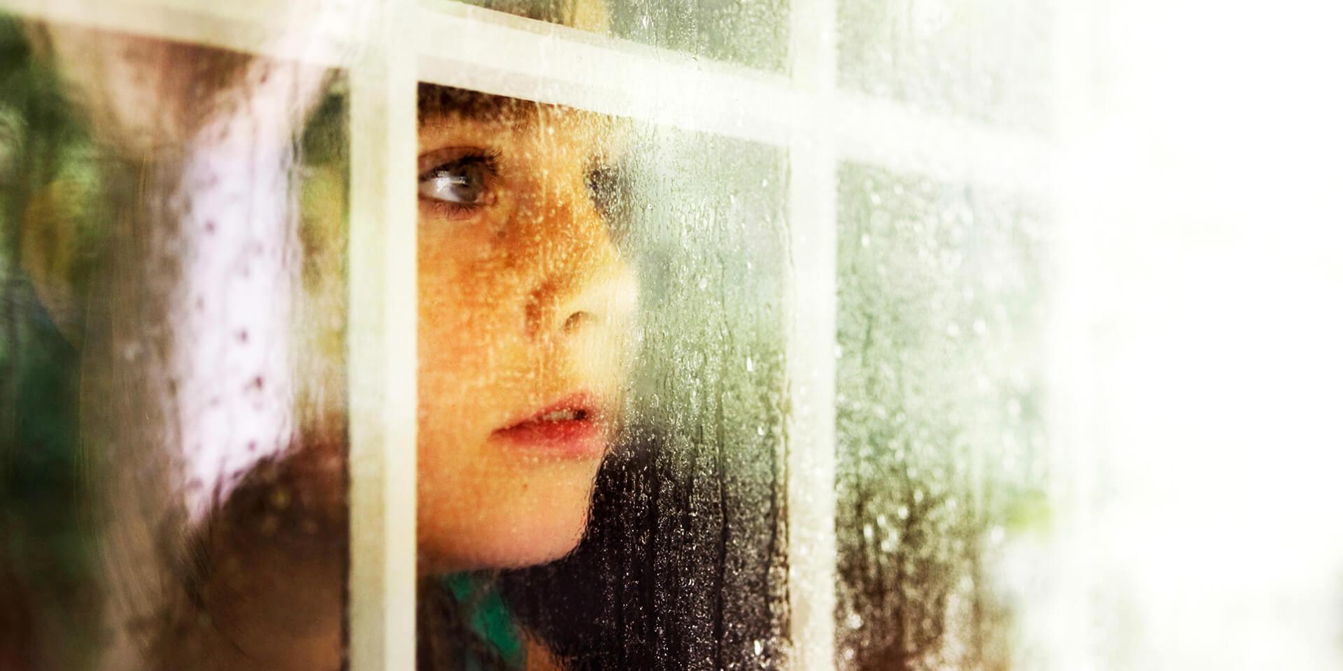 Kind an Fensterscheibe