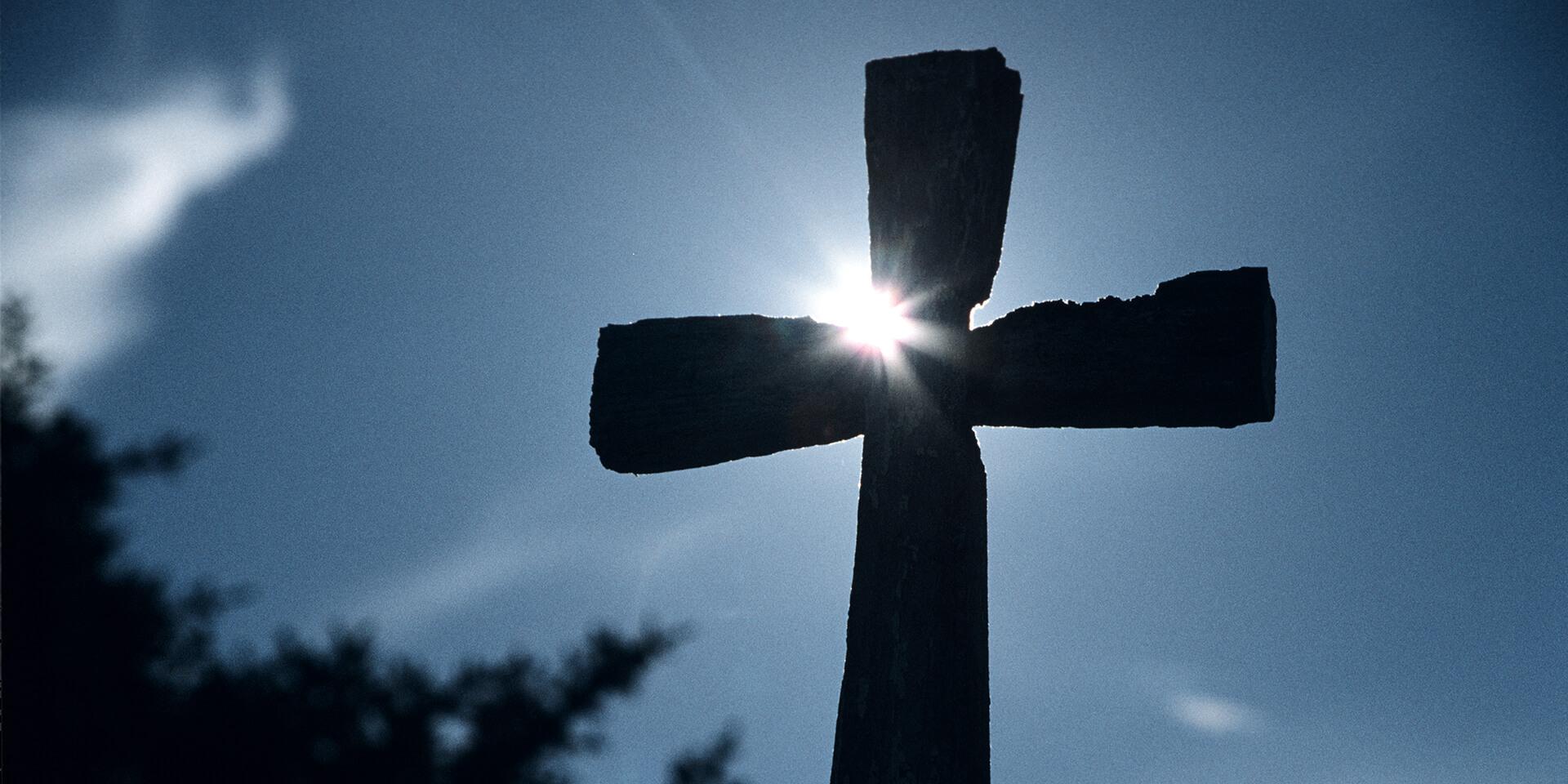 Ein Kreuz, an dem sich Sonnenstrahlen brechen