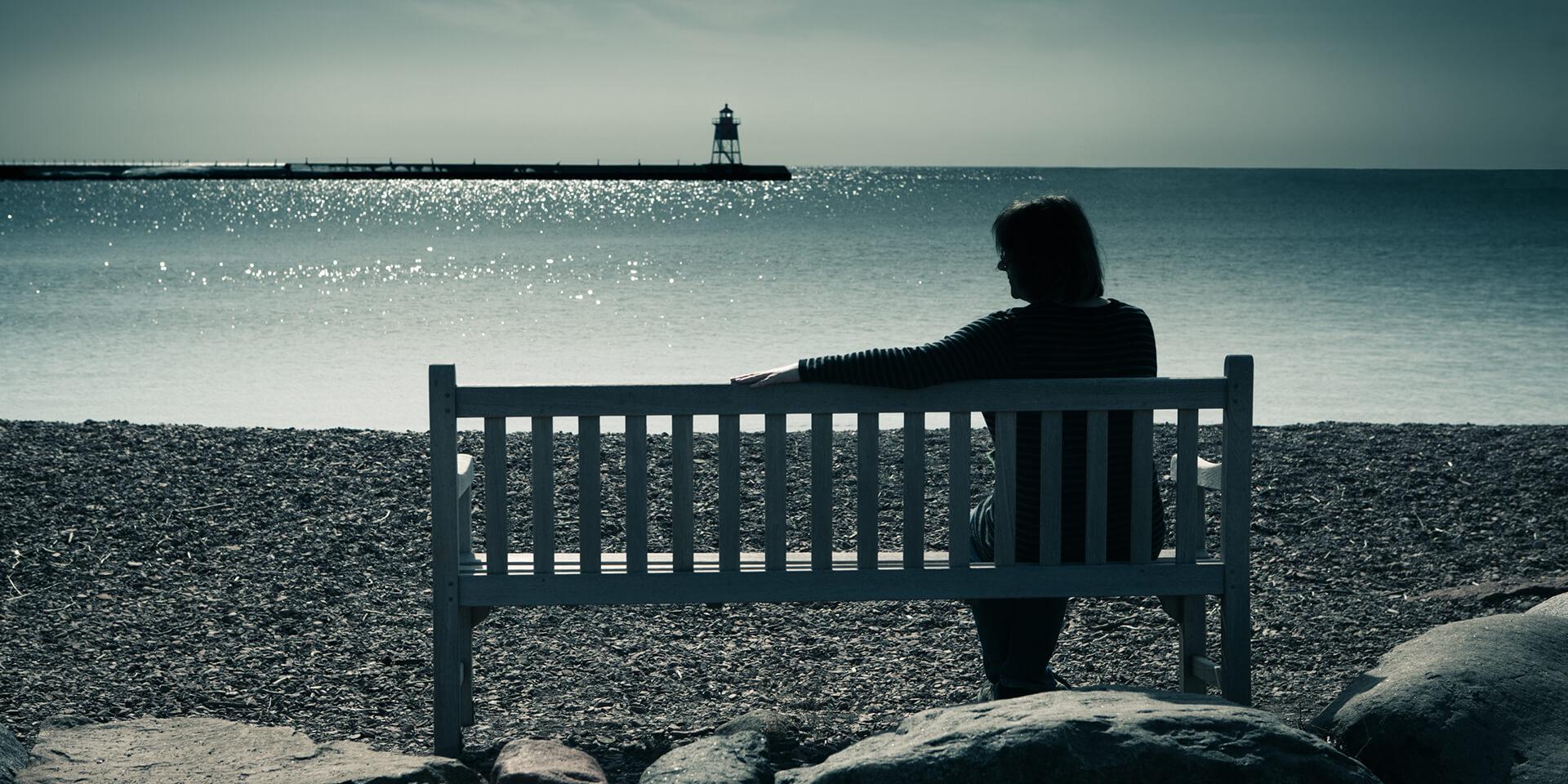 Frau auf einer Bank am Meer