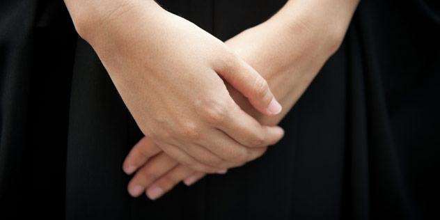 Zu sehen sind die Hände einer schwarz gekleideten Frau.,© iStockPhoto / Atid Kiattisaksiri