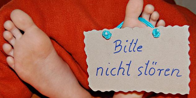 Füße, an denen das Schild 'Bitte nicht stören' baumelt,© Pixelio / Sassi